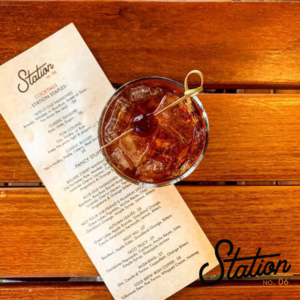 Photograph of cocktail on natural wood table top at Station No 06 in West Allis